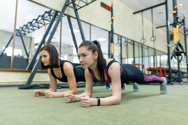 Zwei junge gesunde frauen, die zusammen in der turnhalle trainieren