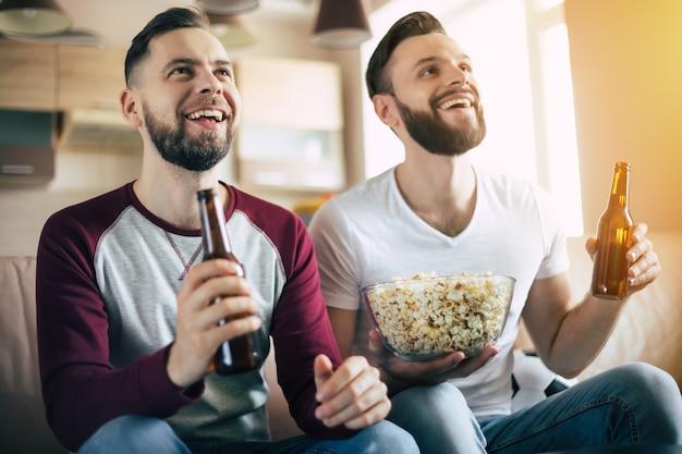 Zwei junge glückliche bärtige freunde, die fernsehen oder ein sportmatch sehen, während sie am wochenende zu hause auf der couch sitzen und bier trinken und snacks essen