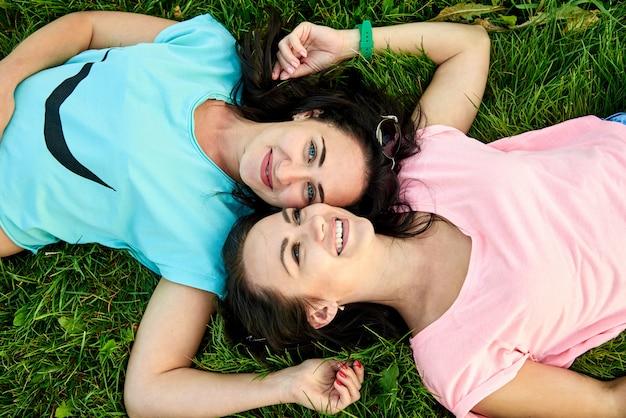 Zwei junge glückliche frauen auf grünem gras.