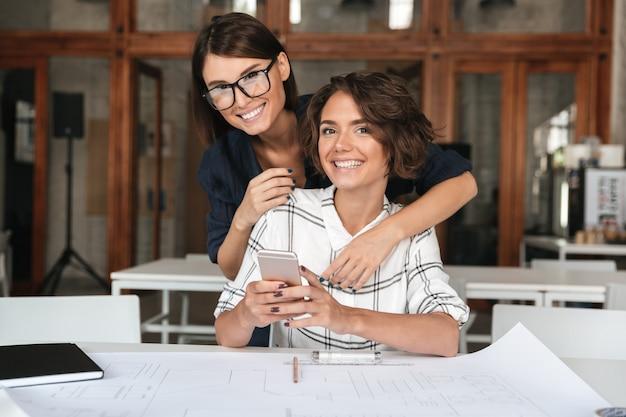 Zwei junge glückliche frauen, die smartphone durch den tisch benutzen