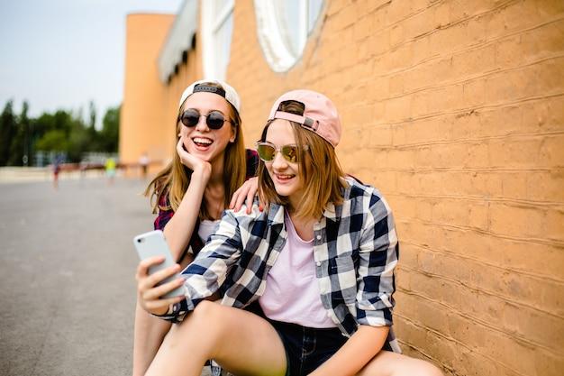 Zwei junge glückliche freundinnen in hipster-outfit sitzen auf longboards und machen selfie am telefon.