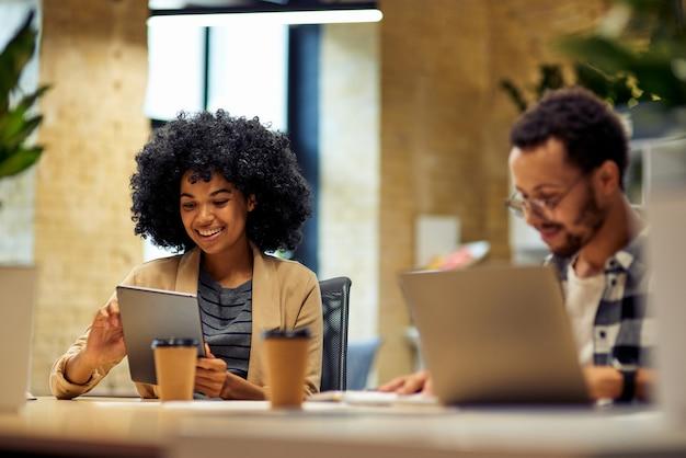 Zwei junge, glückliche, gemischtrassige geschäftsleute, die am schreibtisch sitzen und moderne technologien verwenden, während