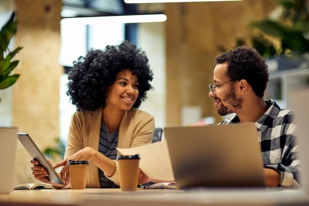 Zwei junge, glückliche, gemischtrassige geschäftsleute teilen frische ideen, die am schreibtisch sitzen und kommunizieren