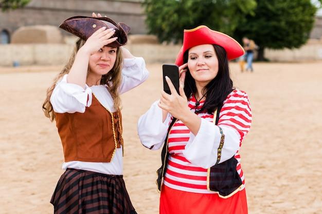 Zwei junge glückliche lächelnde kaukasische frauen in den piratenkostümen putzten sich mit smartphone