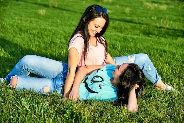 Zwei junge glückliche mädchen liegen auf grünem gras