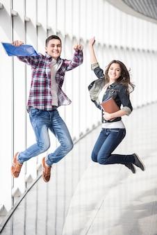 Zwei junge glückliche studenten, die in hochschule springen.