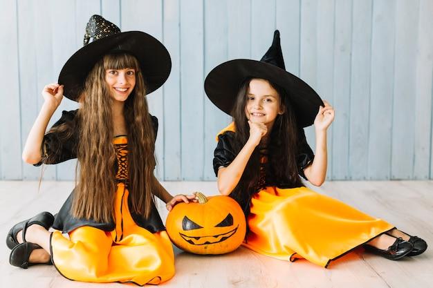 Zwei junge hexen, die auf fußboden auf halloween lächeln und sitzen