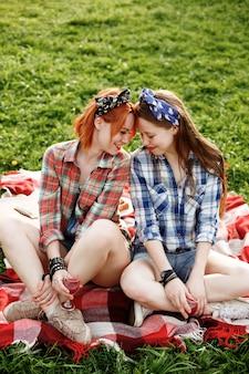 Zwei junge hipster-mädchen, die spaß am konzept des picknicks, der besten freunde haben