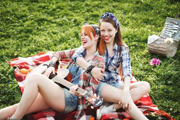 Zwei junge hipster-mädchen, die spaß auf dem picknick haben