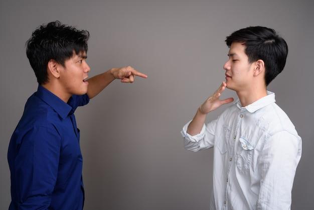 Zwei junge hübsche asiatische männer auf grau