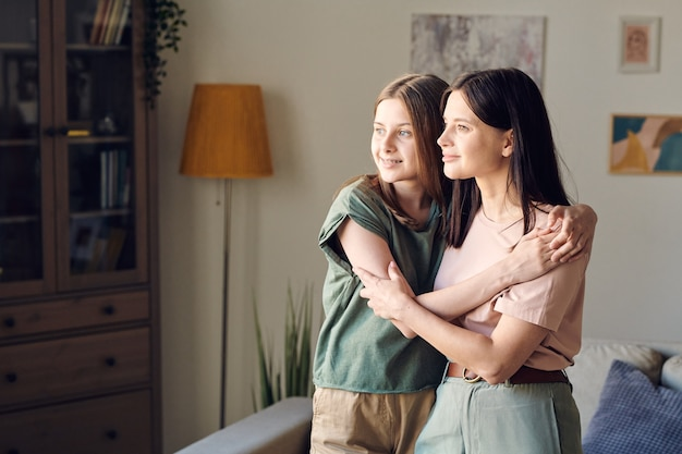 Zwei junge hübsche frauen mit blonden und dunklen langen haaren stehen in umarmung gegen die wand mit gemälden und lampe im wohnzimmer