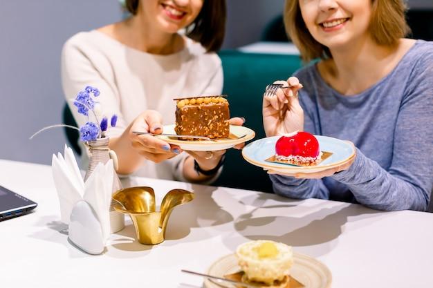 Zwei junge hübsche freundinnen, die spaß haben und nachtische an der bäckerei oder an der konditorei essen