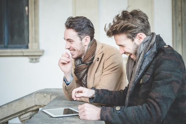 Zwei junge hübsche geschäftsleute mit tablet