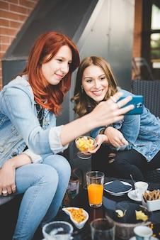 Zwei junge hübsche kaukasische blondine und rothaarige gerade haare frauen sitzen in einer bar