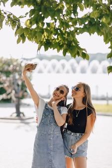 Zwei junge hübsche mädchen auf einem spaziergang im park, die am telefon fotos von sich machen. an einem sonnigen sommertag freude und freundschaften.