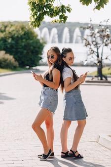 Zwei junge hübsche mädchen auf einem spaziergang im park mit telefonen. sonniger sommertag, freude und freundschaften.