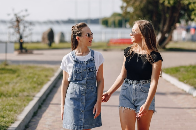 Zwei junge hübsche mädchen auf einem spaziergang im park oder auf der straße