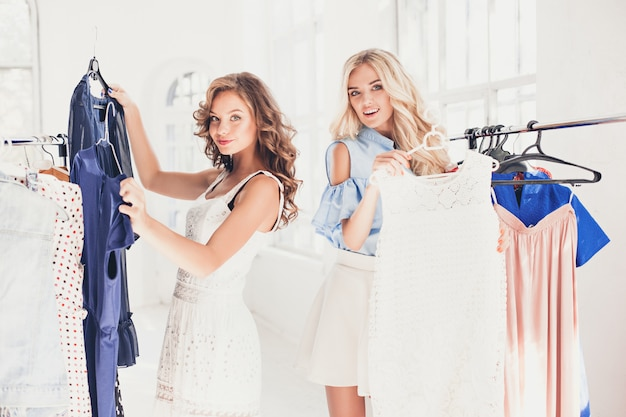 Zwei junge hübsche mädchen, die kleider anschauen und es anprobieren, während sie im geschäft wählen