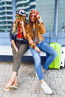 Zwei junge hübsche mädchen, die vor ihren reiseabenteuern die karte erkunden und betrachten, lächeln und spaß vor neuen emotionen haben. bester freund posiert mit seinem gepäck.