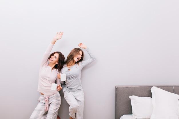 Zwei junge hübsche mädchen im pyjama mit tassen im schlafzimmer auf grauer wand. sie streckten sich und lächelten.