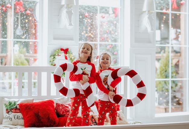 Zwei junge hübsche mädchen in den roten und weißen weihnachtspyjamas und -bögen, die auf großem fenster aufwerfen