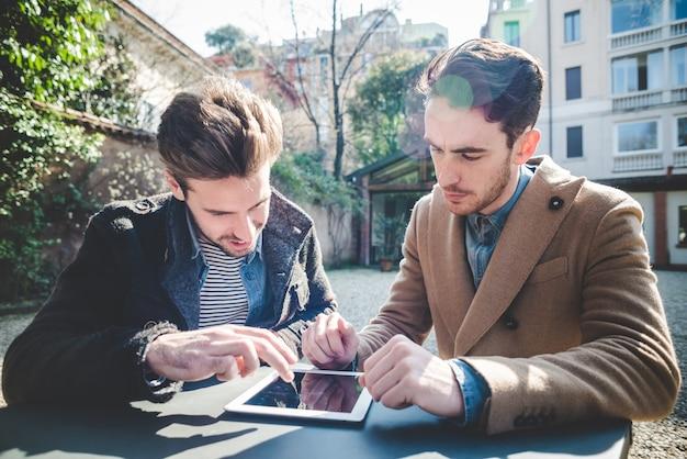 Zwei junge hübsche mode model geschäftsleute mit tablet