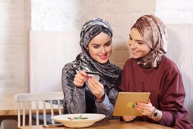 Zwei junge hübsche muslimische frauen sprechen und kaufen online mit einem elektronischen tablet ein
