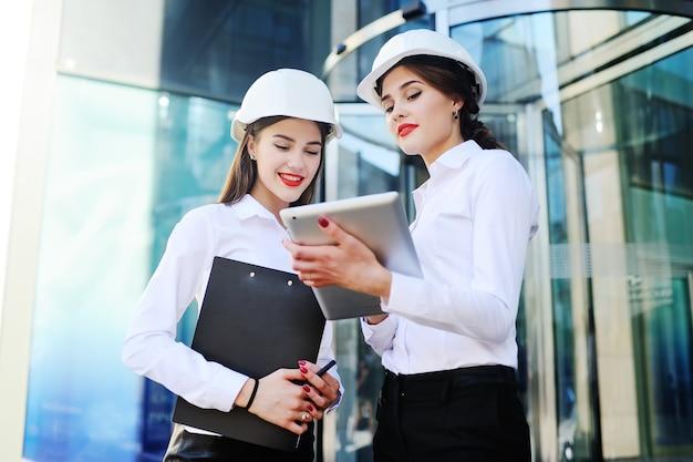 Zwei junge hübsche wirtschaftsfrauen-wirtschaftsingenieure im bau