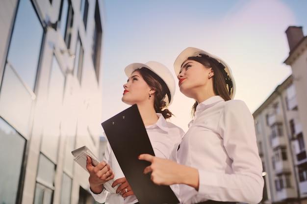 Zwei junge hübsche wirtschaftsfrauen-wirtschaftsingenieure in den bausturzhelmen