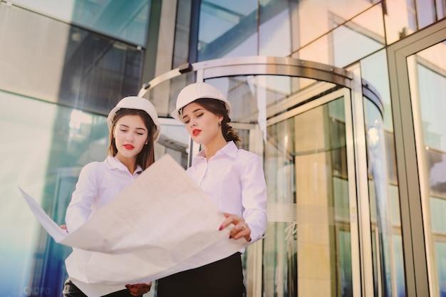 Zwei junge hübsche wirtschaftsingenieure der geschäftsfrauen in den bausturzhelmen mit einer tablette in den händen auf einem glasgebäudehintergrund