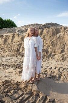 Zwei junge hübsche zwillinge mit langen blonden haaren, die am sandsteinbruch im eleganten weißen kleid, im rock, in der jacke aufwerfen