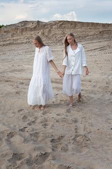 Zwei junge hübsche zwillinge mit langen blonden haaren, die am sandsteinbruch im eleganten weißen kleid, im rock, in der jacke aufwerfen.