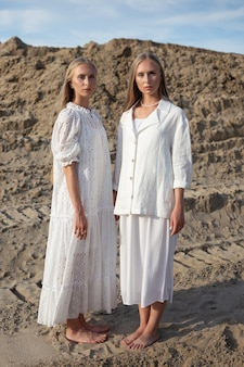 Zwei junge hübsche zwillinge mit langen blonden haaren posieren im sandsteinbruch in eleganten weißen kleidern