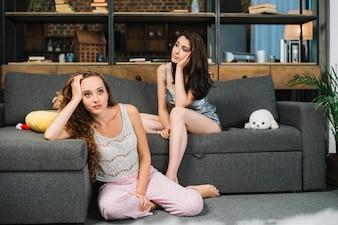 Zwei junge in Betracht gezogene Frauen, die zu Hause sitzen