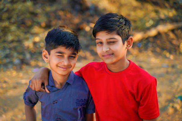 Zwei junge indische kinder zwinkern ihm zu