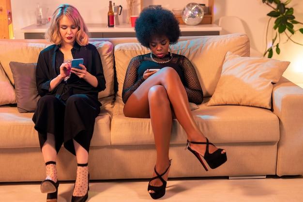 Zwei junge interkulturelle frauen in schwarzer kleidung sitzen auf der couch im wohnzimmer und scrollen durch fotos oder beiträge im netz