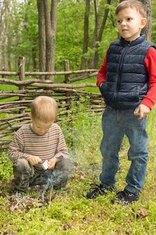 Zwei junge jungen lernen überlebensfähigkeiten, die versuchen, ein kleines lagerfeuer zu entzünden
