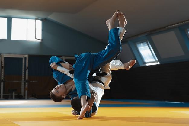 Zwei junge kämpfer im kimono trainieren kampfkunst im fitnessstudio