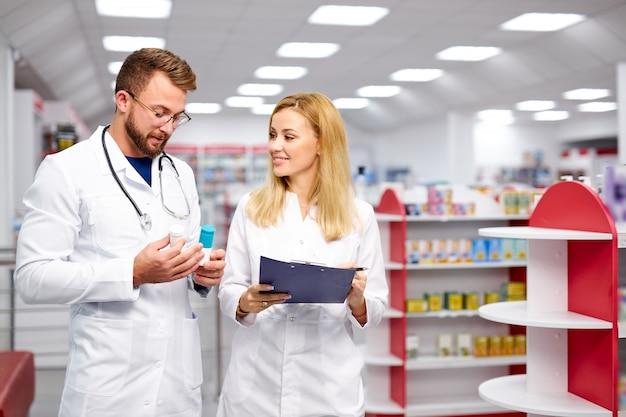 Zwei junge kaukasische apotheker diskutieren über medikamente