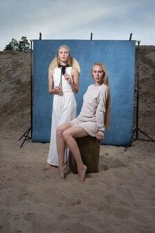 Zwei junge kaukasische hübsche zwillinge mit dem langen blonden haar, das im sandsteinbruch in eleganter weißer, beiger kleidung vor blauem hintergrund aufwirft