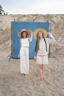 Zwei junge kaukasische hübsche zwillinge mit langen blonden haaren, die im sandsteinbruch in eleganten weißen, beigen kleidern und hüten vor blauem hintergrund aufwerfen