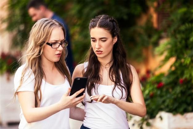 Zwei junge kaukasische mädchen besprechen etw und schauen auf dem smartphone mit ernsten gesichtern
