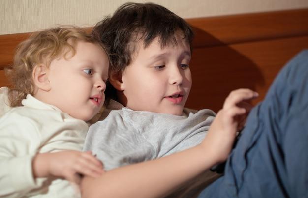 Zwei junge kinder, die mit einer tablette spielen