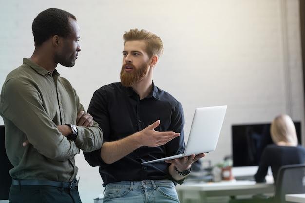 Zwei junge kluge geschäftsleute diskutieren neues projekt