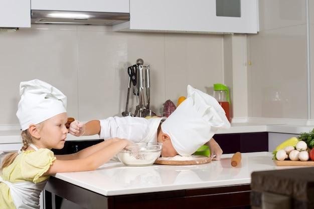 Zwei junge köche haben spaß in der küche