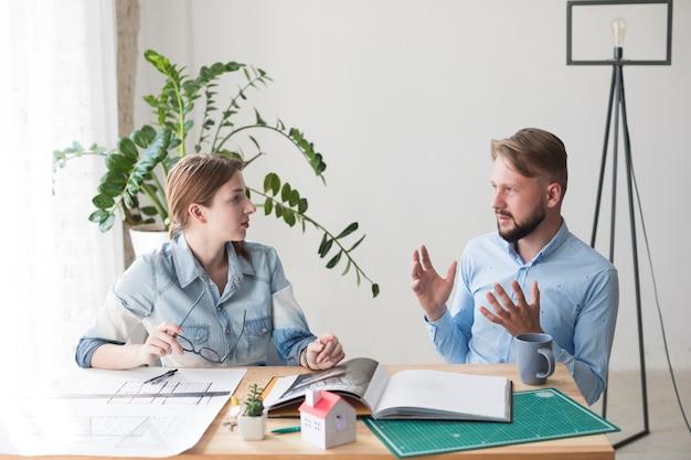 Zwei junge kollegen, die etwas im büro besprechen