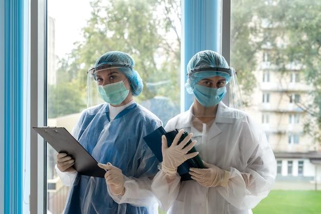 Zwei junge krankenschwestern, die während einer coronavirus-pandemie im korridor einer modernen klinik in schutzkleidung posieren