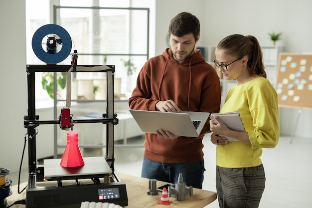 Zwei junge kreative designer, die nach neuen online-ideen für kreatives projekt suchen, während sie vor 3d-drucker stehen