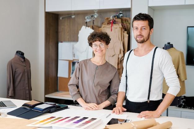 Zwei junge kreative designer von kleidungsstücken, die während der zusammenarbeit am schreibtisch stehen