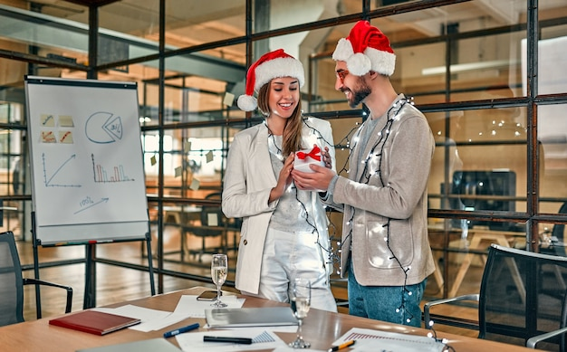 Zwei junge kreative menschen, die weihnachtsmützen tragen, tauschen am letzten arbeitstag geschenke aus.